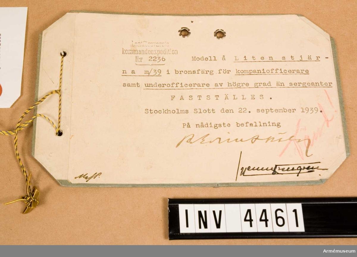 """Gradbeteckning m/1939, kompaniofficer/underofficer högre än sergeant. Av metall. Femuddig stjärna. Anbringas på var axelklaff 1-3 stjärnor, beroende på tjgr, medelst en klammer, fastlödd på baksidan. Vidhängande etikett anger fastställelsedag: """"Stockholm Slott den 22. sept. 1939 Per Edvin Sköld /Henry Kellgren"""".Den 3 juli 1945 fastställdes stjärnknapp m/45 f uoff att anläggas av förvaltare, fj och serg. Liten stjärna m/39, bronsfärgad, kom därför att från detta datum anläggas av koff endast."""