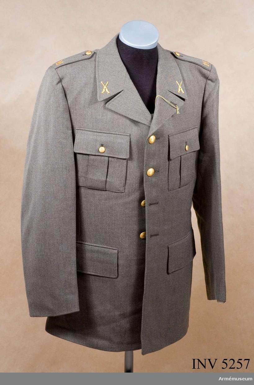 Skick som ny. Storlek: 104. Av samma snitt som uniform m/1939. Daglig dräkt av gråbrungrönt tyg. Bärs till mörkt gråbrungröna byxor. Tjänstetecken mattförgyllda.