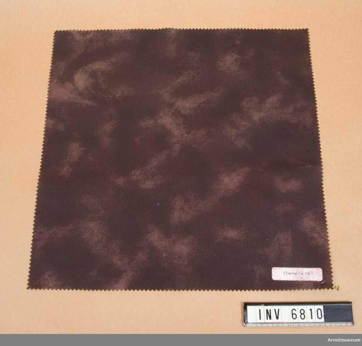 Prov av väv till regnkappa, FMV. 1981. Mått 300 x 170 mm. Material under utveckling av lättare kvalitet avsedd för  regnkappa. Materialet är kamoflagemönstrat med beläggning av  polyuretan/acrylat eller teflon.