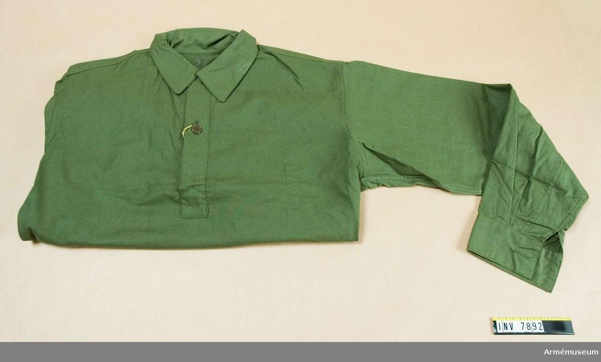 Är sydd i olivgrönt bomullstyg med flossad avigsida. Har fast krage och sprund med två knappar. Enkel manschett. Sprund i sidorna.