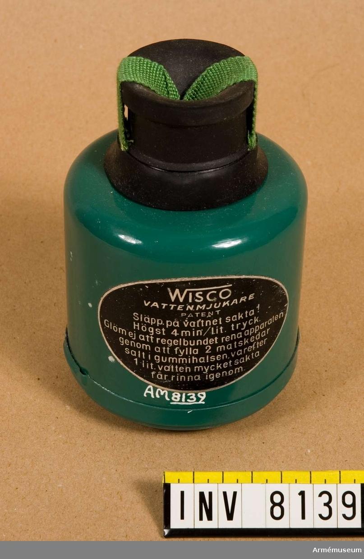 """Vattenmjukare Wisco.Tillverkad av grön och svart plåt och gummi. Klistrad etikett  """"Wisco vattenmjukare Patent"""". I botten med vit oljefärg """"C"""". Apparaten skall sättas på en vattenkran. Vattnet får rinna igenom med högst 4 min/liter (sic!) tryck. Rening av apparaten görs med 2 matskedar salt som läggs i gummivalsen varefter en liter vatten sakta får rinna igenom. Bruksanvisning finns i  förpackningen.Ingår i fotomaterielsats 7 låda 2."""