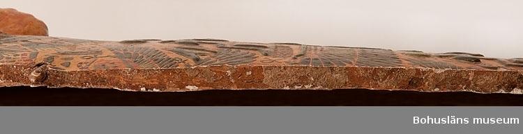 Antropoid mumiebräda dekorerad i flera färger på en gul bakgrund. Brädan lades på mumien inne i kistan. Brädan avbildar den avlidne bärandes en peruk och under hakan finns idag ett hål där ett lösskägg (?) suttit. Ett halsband är avbildat på den övre delen av bröstkorgen där även de korslagda händerna kommer fram. På kroppens mittdel finns två horisontella band med guden Amun-Ra avbildad samt hieroglyfer. Dessa två band åtskiljs av den bevingade himmelsgudinnan Nut. På brädans nederdel fyra horisontella band med gudar och hieroglyfer.  Ur Knut Adrian Anderssons katalog II Uddevalla - Musei - Historiska - Samlingar: E: Utländska föremål De Etnografiska föremålen upprättad år 1916: No 63 Lock till Sarcofag = Mumiekista från omkring 1200 år före Kristi födelse. Kistan omslöt en Ammons-präst (avmålad å locket) funnen i Egypten vid Thebe (=Deir el Bahari) Skänktes till U-A Museum i mars 1910 av herr Carl Christiansson i Paris (f. d. Uddevallabo)  Ur handskrivna katalogen 1957-1958: Lock t. mumiesarkofag Egypt.  L.175. Br. 32,5. Trä målad i färg. Något skadad, en lös bit.  Lappkatalog: 100 Se visitkortsporträtt på Carl Christiansson, UMFA53226:0842. Se även fotografi UM000546 och UM000547 (saknas).