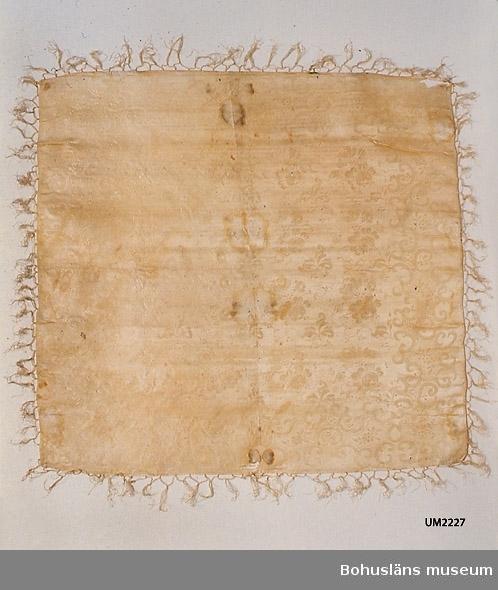 """571 Användningstid 1846-1900? 503 Kön KVINNA  Kvadratisk jacquardvävd sidenschalett i mycket ljust gult (troligen gulnat vitt?), med ett blommönster av rosor eller pioner utspridda i mittspegeln och en snirklig bård runt om. Påknutna fransar. Svart stämpel i ena hörnet: """"SVENSKTIL"""" läsbart, resten borta p g a hål i tyget. Tillverkningstiden uppskattad med ledning av stämpeln. Innan sidenschalarna fick säljas skulle de kontrolleras och få en hallstämpel, från början en kvalitetsstämpel, men fr. o. m. 1832 intygade stämplingen endast svensk tillverkning. Efter 1846 då hallstämpeln drogs in försågs varorna med svensk tillverkningsstämpel. Förordningen om detta varade till 1862. Troligen har schalen en stämpel av det senare slaget. Hål vid stämpeln och nära ytterkanten på ena sidan. Bristningar på flera ställen i gamla viklinjer. Flera stora fläckar på mitten. Små fläckar på olika ställen.  Litt; Håkansson, Elin, Sidenhalsdukens bruk och tillverkning ur """"Sörmlandsbygden"""" 1933. Lindvall-Nordin, Christina, Mossrosor och hjärtblomster ur Kulturens årsbok 1969, Lund. Wulfcrona-Dagel, Marie Louise, Schaletter och halskläden i Nordiska museet vävda hos K A Almgrens sidenväveri i Stockholm, uppsats för fortsättningskurs i etnologi, Stockholm 1979.  Ur handskrivna katalogen 1957-1958: Schal  av gult siden Mått c:a 85 x 81 cm. Gult mönstrat siden m. fransar. Fläckar o smärre hål. Blekt.  Lappkatalog: 76"""