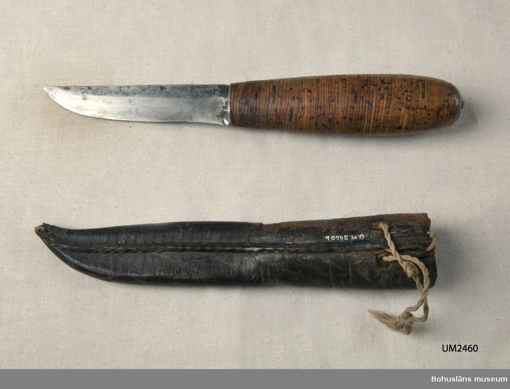 Knivens skaft är gjort av näver som packats tätt kring tången. Slida av svartfärgat läder med inpressad dekor; skador på narvsidans  ytskikt. Upphängningsögla saknas. I bruksskick.  Ur handskrivna katalogen 1957-1958: Slidkniv m. näverskaft o läderslida Kniven a) L. 19,8 cm; skaft av näverplattor(?) m. mässingsbeslag. Slidan b) L. 17,5 cm; av svart läder; trasig. Kniven hel.  För uppgifter om givaren, se UM002249.