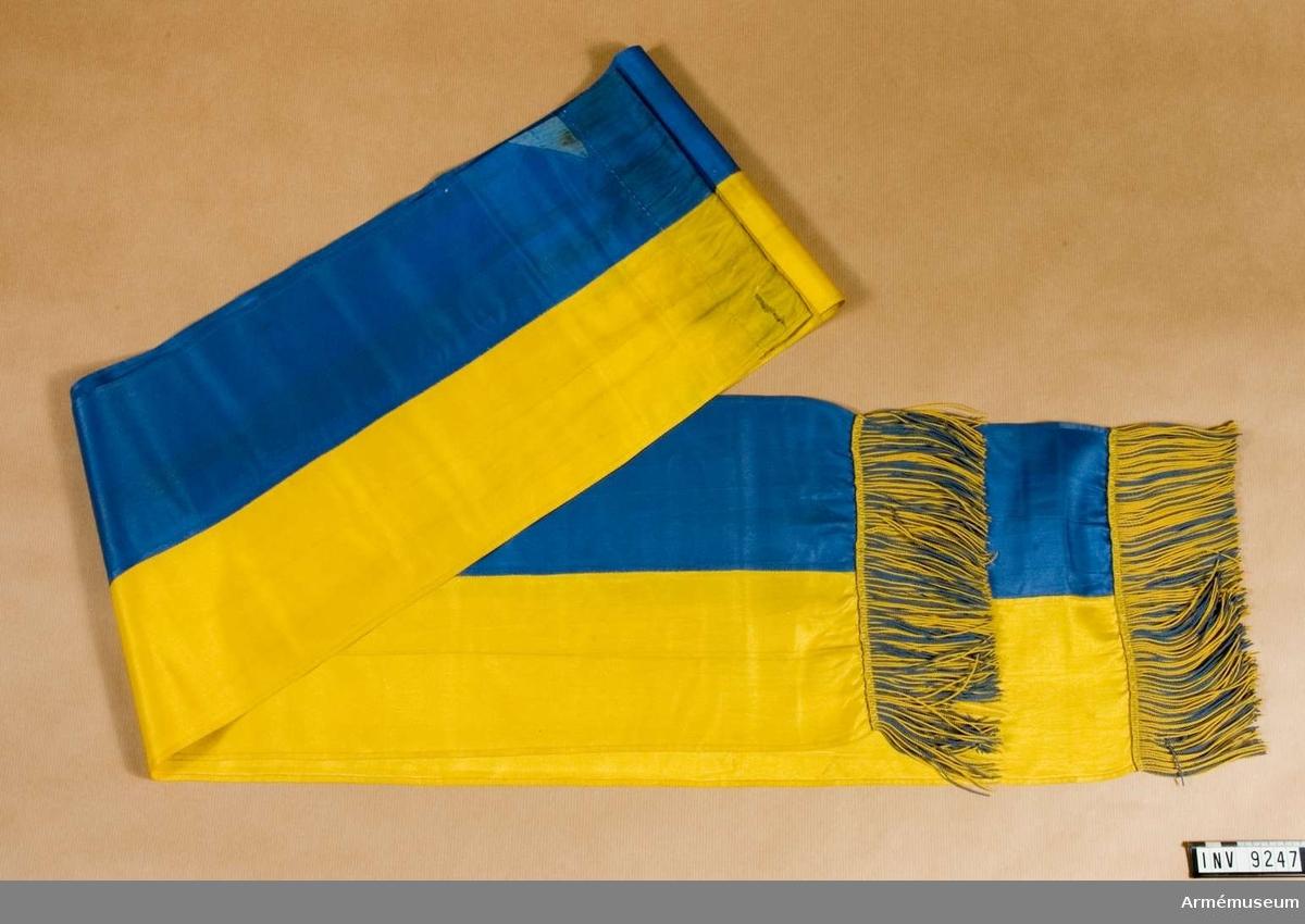 Sydd för hand av hälften blått och hälften gult siden med på kortsidorna en enkel frans blandad i gult och blått silke.