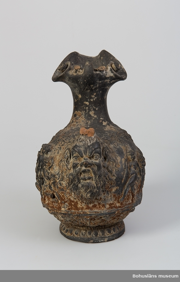 Ur handskrivna katalogen 1957-1958: Lerurna fr. Pompeji Bottenmått: 14,8 x 12,5. H. c:a 40,5 Svart keramik. Handtag i form av människa. Lagad.  Lappkatalog: 100