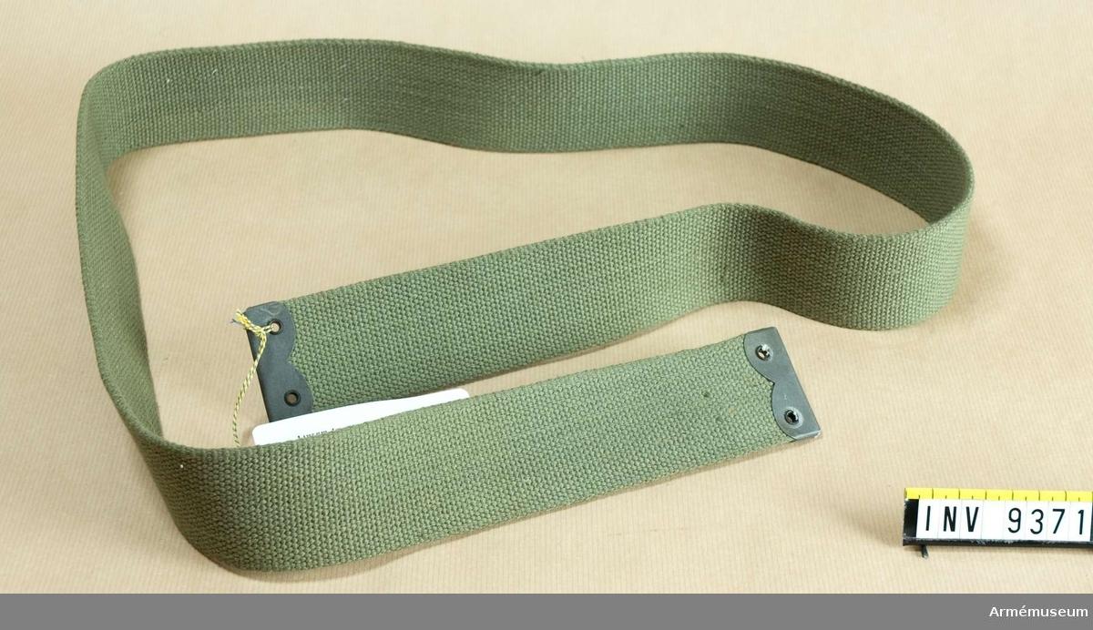 Av grönt textilband, cord. Metallförstärkning i de båda  ändarna. Gåva från FMV i Solna.