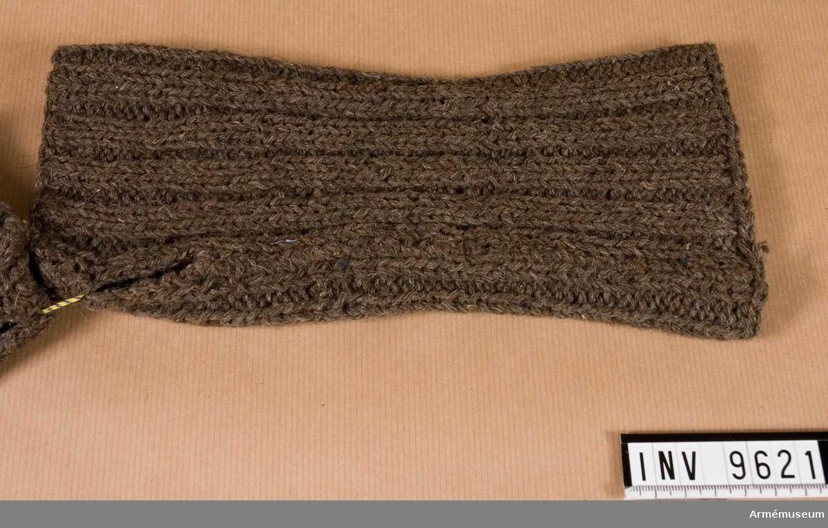 Mudd m/1944.Handstickad mudd i resårstickning. Ihopsydd på längden och med en kvarlämnad öppning 40 mm lång för tummen.  Samhörande nr är 9605-9650 + 9659-9666. Ipar 9621-9622.