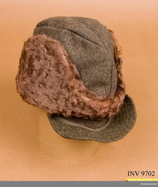 Av kommisskläde med grått fårskinn och med skräm och öronskydd och bakrem. Har vadderat foder av grått bomullstyg.