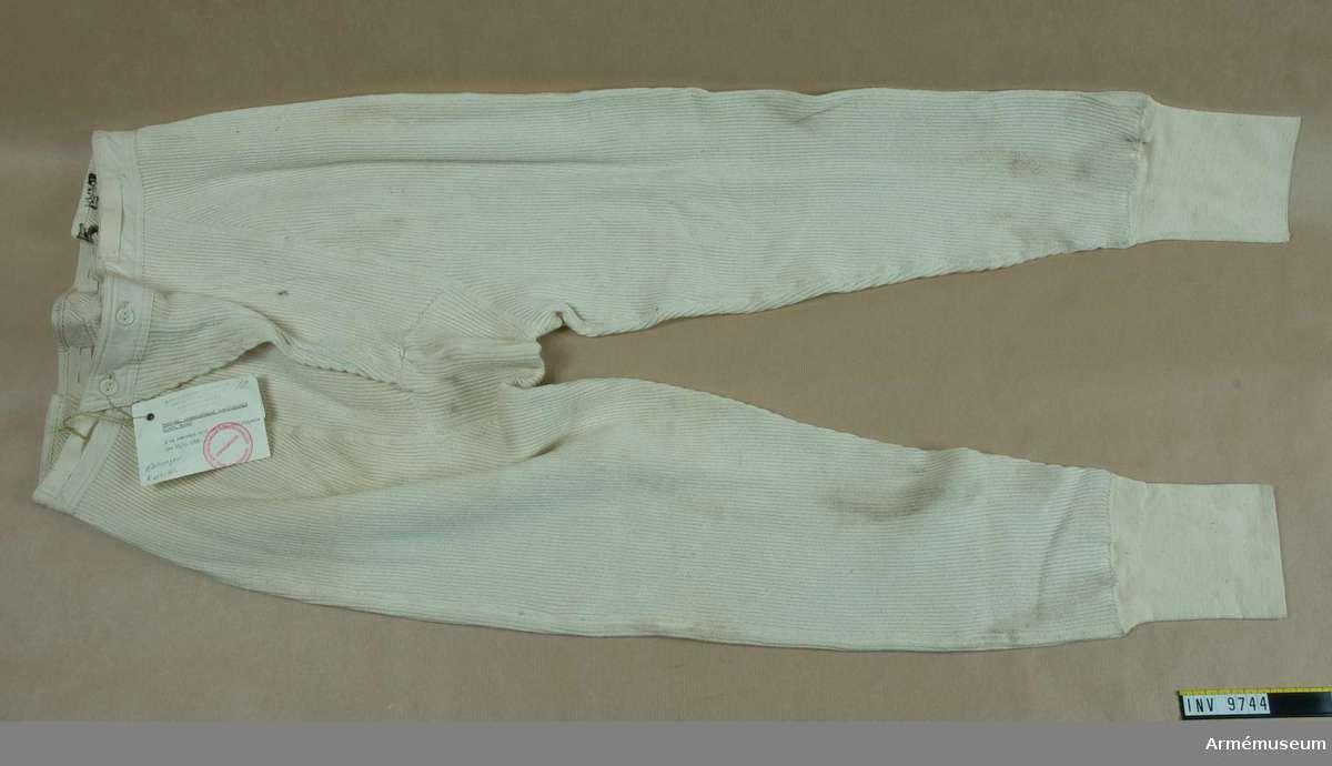 Av patentstickat halvblekt bomullsgarn. Har linning i midjan av bomulstyg och med resårband. Finare stickad mudd nedtill  på benet.