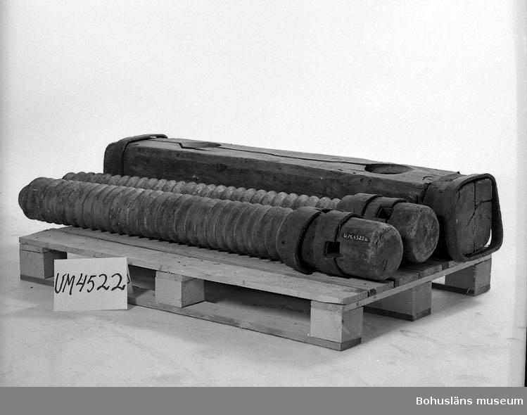 Ur handskrivna katalogen 1957-1958: Tre delar av halmpress a) En grov stock, m. 2 gängade hål. L. 133; Tj. 26 x 22 cm; förstärkt m. beslag och genomgående bultar. b) Skruv av trä, passande till föreg. L. c:a 140; gänggångens D. c:a 15 cm. c) Skruv som föreg. L. och D. som föreg. Båda har en grövre klump i ändan, m. 2 genomg. hål och beslagen m. järnringar. Föremålen hela.  Lappkatalog: 51