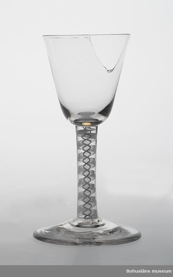 """Glasets ben har spiraler i vitt; """"latticinospiraler"""". Troligen engelsk tillverkning.  Ur handskrivna katalogen 1957-1958: Vinglas m. inl. flätad dekor Mynningsdiam.: 6,7. H: 15,5. Rund fot. Skaft med målad dekor. Skålen sönder, foten skadad."""