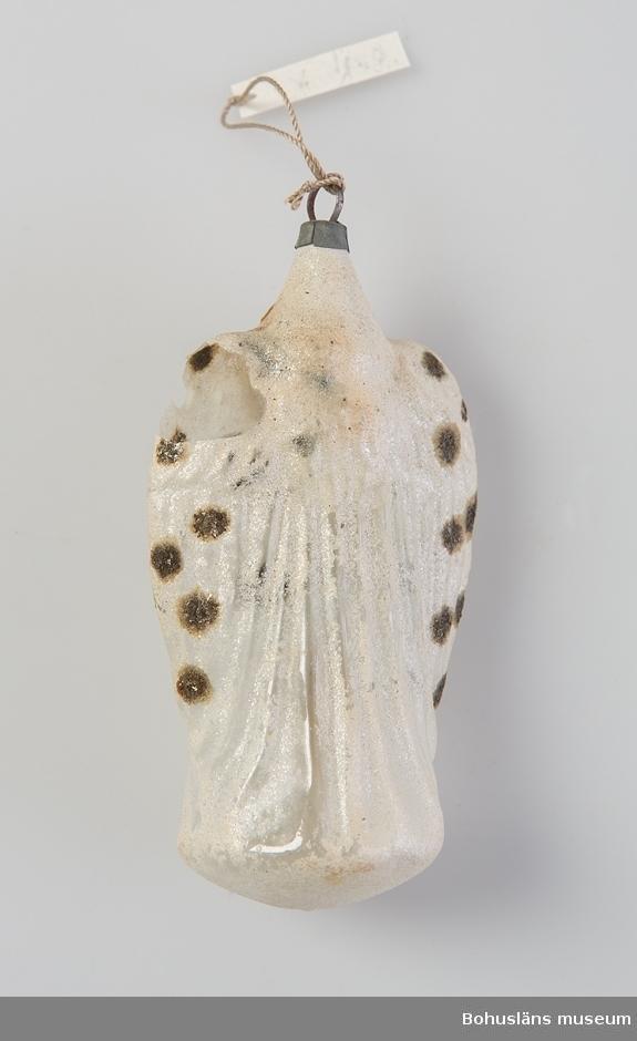 """Ängel, gjuten i glas med små vita flingor av glittrande färg applicerat på ytan; prickar av gnistrande mineral. Ängelns ansikte är ett fastlimmat pappersbokmärke (litografiskt framställt). Ögla för upphängning. Skadad på ena """"axeln"""". Clara Nilsson (1866 - 1946) var mormor till givarna som var systrar. Prydnaden avsedd att hänga i julgran. Den hör till den skörare skaran av prydnader."""