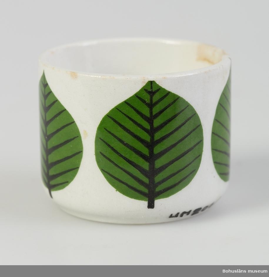 "Cylinderformad med tryckta gröna, stiliserade löv. Ur servis ""Berså"". Formgivare: Stig Lindberg."