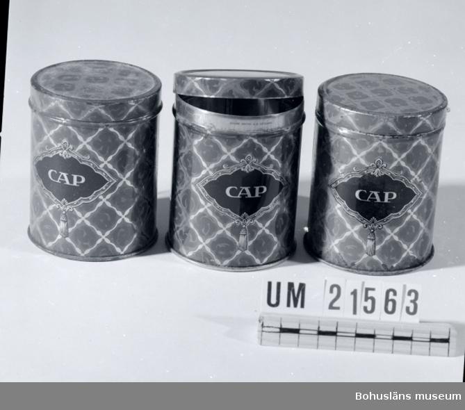 """594 Landskap BOHUSLÄN  CAP """"Familjeblandning"""" netto 1/4 Kg. Burkarna är blåmålade med guldfärgat rutmönster över hela burkarna. Ett svart medaljliknande märke på framsidan med bokstäverna """"CAP"""". CAP står för Claes August Pettersson, som startade sin verksamhet 1895 under firma FRANSKA KONFEKTFABRIKEN C. August Pettersson. Dessa burkar hör till fabrikssortimentets mest uppskattade produkter.  Mer information: Se UM21020.  Litteratur: S. Hagman, Tidernas godis, 1986.  UMFF 31:11"""