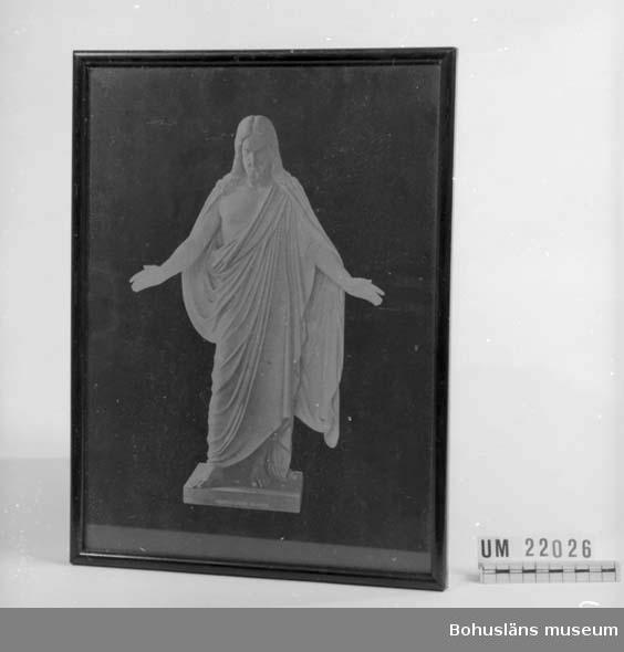594 Landskap BOHUSLÄN  Bilden föreställer skulptur av Kristus i gulvit färg mot svart bakgrund.  Märkt på sockelytan: No 5. Thorvaldsen: Kristus.  Rödbrunt färgad rund smal trälist samt glas, spikad grå bakpapp.  Ståltråd och snöre på baksidan för upphängning.         UMFF 71:9