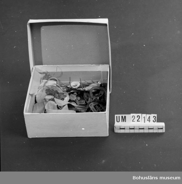 """594 Landskap BOHUSLÄN  Lådan innehåller:Nycklar 5 st.klackjärn 2 st.fingerborg 1 st. brosch 2 st. Märke Röda Kors med rosett, märke 3 st.med texter: """"Folklandskamp Sverige-Finland"""",""""Var Redo"""",""""Frihetens värn"""", ring av koppar, ring av ben, inbränt: """"Marstrand"""", spänne 3 st. hattnål, korkskruv (miniatyr), knappar 5 st.små, 1 st.kragknapp,nål av ben, nyckelring, beslag till nyckelhål, band av papper, ljusmanschett:1 st.av järn, 1 st.av plast, skrivstift 4 st. häftstift,  kokard 2 st. fågel (talgoxe av lera), hårnålar.  UMFF 84:3"""