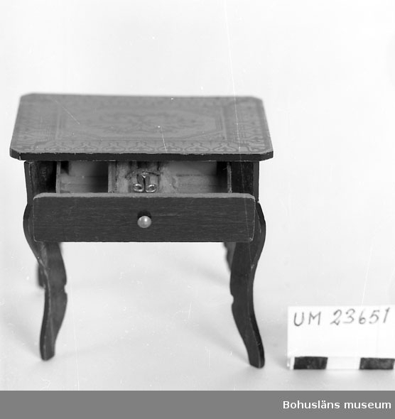 594 Landskap BOHUSLÄN  Fyra profilsågade ben. Bordet betsat för att likna mahogny. Bordsskivan målad nyrokokodekor i guldfärg. Låda i sargen innehållande liten sax i bly.  Neg. nr UM 148:10