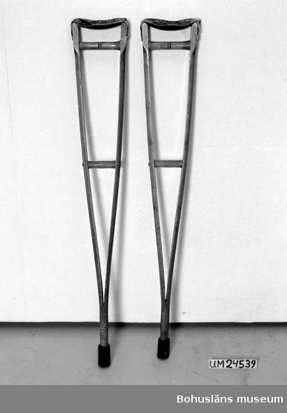 571 Användningstid *1910-20 ? 594 Landskap BOHUSLÄN  Två stycken parallella trästänger vilka går ihop nertill i en gummiklädd del.  Två stycken tvärgående handtag av trä mellan de två stängerna.  Den del som skall vila mot armhålan är klädd med läder.