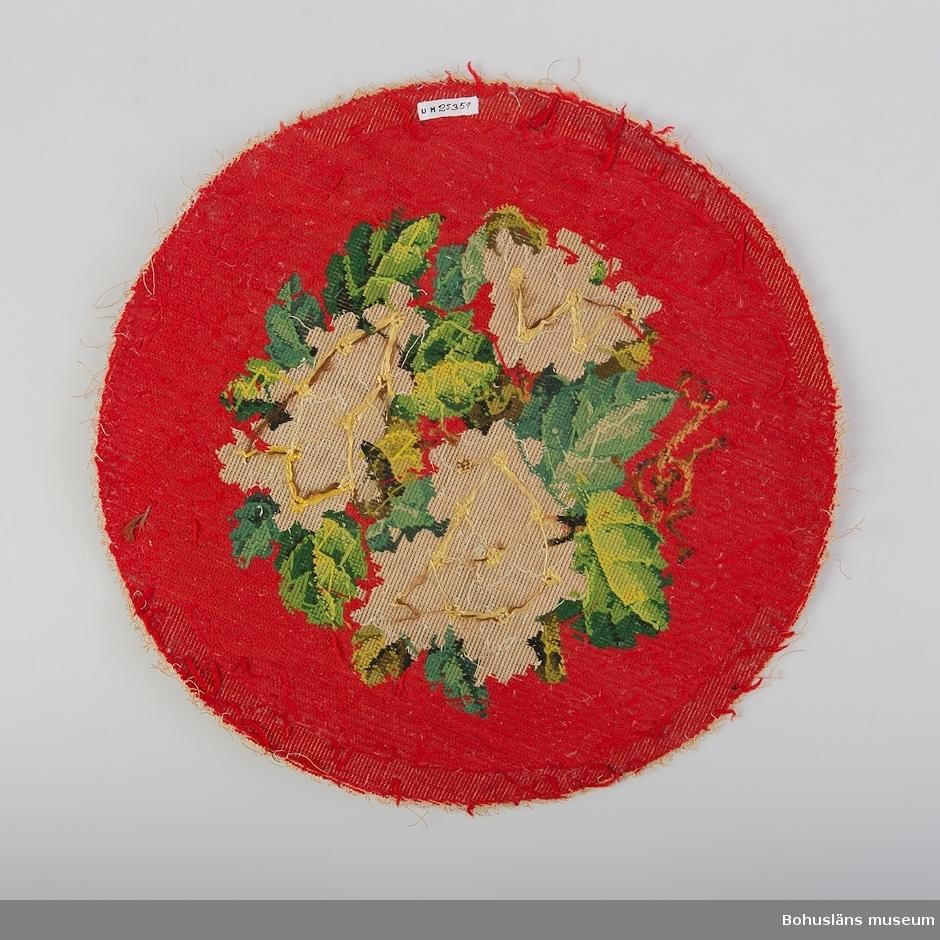 Möbelklädsel broderad på stramalj i korssöm med blommor sydda av vita, mjölkvita, genomskinliga och grågröna pärlor samt brunt och gulgrönt silke i blommornas mitt och med blad av ullgarn i olika gröna nyanser. Röd  bakgrund. Blad/bakgrund i korsstygn. Rester av dun/fjäder på baksidan. Har suttit på brudpall för brudgum. Anemoner som symbol för brudgummen. Sedermera under 1900-talet använd som soffkudde med svart tyg som baksida hos familjen Alban Thorburn (givarens familj). Familjen Jacobi ingift i familjen Thorburn bl a genom givarens farmor Alma Thorburn, född Jacobi. Hör samman med UM025360. Stramaljen kom år 1854 enligt litteraturen, datering utifrån det. Några pärlor är bortslitna. Traskanter.  Litteratur: Fleming/Lindvall-Nordin m. fl. Rosor och violer i korsstygn, LT Stockholm 1983, sid. 41-42.  Fredlund, Jane. Stora boken om livet förr, ICA-förlaget Västerås 1981, sid. 98-105. Rosenknopp och yllestopp, utställningskatalog från Helsingfors Stadsmuseum 1986.  Westerdahl, Elisabeth. Pärlbroderade prydnader, Antik och auktion nr 4 1994.