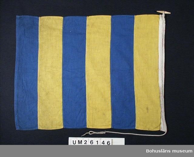 """Föremålet visas i basutställningen Kustland, Bohusläns museum, Uddevalla.  Sexdelad i varannan rad blå, varannan rad gul.   Betyder: """"Jag behöver lots"""".  På fiskefartyg som fiskar i närheten av varandra betyder flaggen: """"Jag tar hem redskap"""". Använd för fartygssignalering på  Ångfartygs AB Bohuslänska Kustens båtar. Användning se UM026139  Personuppgifter se UM026024"""