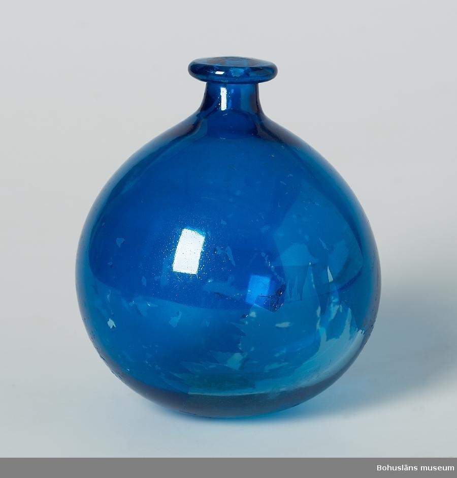 Blåmålat glas, filmskiktet delvis avflagat. Försedd med en utskjutande knopp, troligen för fästa den i fiskgarn. Möjligen dansk tillverkning.