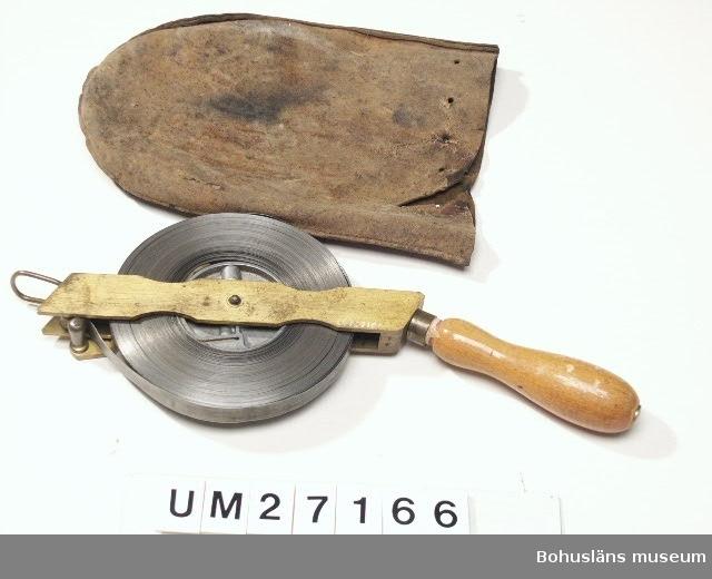 """Utdragbart måttband av stål i stålkapsel vev och på trähandtag. 50 meter  med mått i meter. Måttbandets bredd: 15 mm. Till måttbandet hör ett läderfodral med hål i kanten för  stängningssnöre, vilket saknas, UM27166:2. Måttbandet märkt på vevens insida """"STEWE QVALITÄT 50m"""".  Verktygsuppsättningen är skänkt av Lennart Bornmalm, son till GB.  LB ingår i den arbetsgrupp som dokumenterar fiskebåtsvarv och fiskebåtar i Bohuslän i samarbete med Bohusläns museum.  Litt: Ohlén, Björn: """"Fiskebåtsvarv i Bohuslän - industri- historisk dokumentation av Hälleviksstrands varv, Rönnängs varv, Studseröds varv."""" Bohusläns museum. Rapport 1999:43.  För ytterligare uppgifter om brukare, tillverkare och samtidiga förvärv, se UM 27031."""