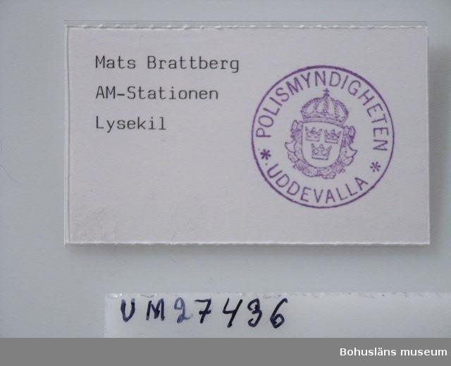 """Föremålet visas i basutställningen Kustland,  Bohusläns museum, Uddevalla.  571 Användningstid APRIL 1990 Namnbrickan består av ett rektangulärt fodral i genomskinlig hårdplast som på baksidans överkant överlappar ca 5 mm. Härunder sitter en säkerhetsnål i stansade hål horisontellt placerad. Inuti fodralet sitter en vit papperslapp med perforerade kanter. På högerhalvan sitter en rund stämpel inom vilken polismyndighetens vapen står omgivet av texten """"POLISMYNDIGGHETEN UDDEVALLA"""". På maskin står på vänstra halvan textat: """"Mats Brattberg AM-stationen Lysekil"""".  Brickan bars av givaren såsom passersedel i Lysekils hamn dagarna efter brandkatastrofen på passagerarfärjan """"Scandinavian Star"""" den 6 - 7 april 1990.   För beskrivning av denna händelse och kring givarens egna upplevelser under ordinarie arbetet under dessa svåra dagar, se intervju med Mats Brattberg i oktober 2000, Bilagepärmen UM27436.  Fartyget Scandinavian Star var en Bahamasregistrerad kryssningsfärja med rutt Oslo - Fredrikshamn i dansk-norska redaren Da-No-rederiet.  Fartyget började brinna, sannolikt  p. g. a. en anlagd brand, natten mellan den 6 -7 april 1990 i Skagerack, haveriplats 11 grader väst om Väderöarna, norra Bohuslän. Fartyget hade 91 besättningmän och 430 passagerare. 158 passagerare omkom. 340 personer evakuerades i ett dramatiskt räddningsarbete med flera medverkade fartyg. Den brinnande färjan bogserades sedan in till kaj i Lysekil där brandpersonal fullföljde släckningsarbetet och förde iland de omkomna. Dåliga förehållande n ombord medverkade till katastrofen; stora  brister i brandsektioneringen, otränad besättning, språksvårigheter och bristfällig brandberedskap.  Brickan är insamlad i samband med SAMDOK""""s projekt """"Svåra saker. Berättelser som upprör och berör"""" 1999 och den vandringsutställning med samma namn som turnerade i Riksutställningars regi december 1999 - september 2000 runt hela Sverige.   På Bohusläns museum visades utställningen en vecka våren 2000. I samband med detta """