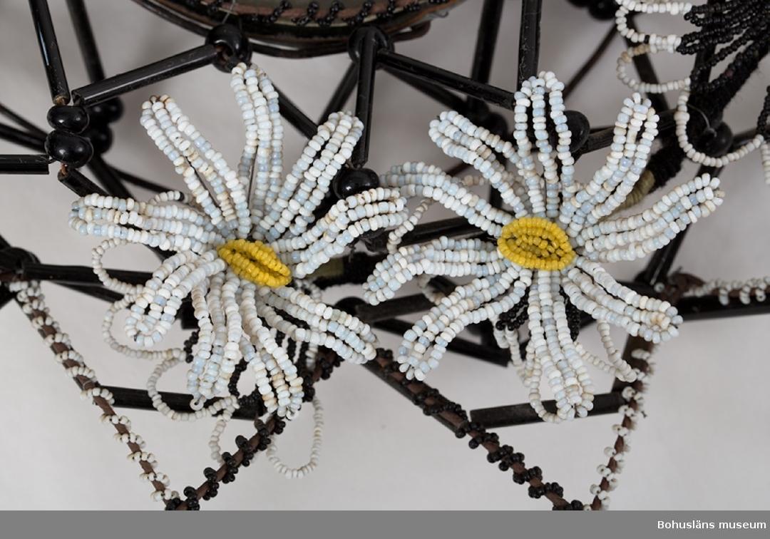 """Oval krans gjord på stomme av järntråd i en konstfull hopflätning, den inre delen i två våningar. Stommen är därefter klädd med svarta glaspärlor - stavar och runda samt med vita svarta och gula små pärlor, uppträdda på textil tråd som virats runt stommen. Kransens mitt pryds av en silvermålad pappdekoration som vilar på en platta av tunn plåt och papp. Dekorationen är utformad som ett kors på en gravkulle, skyddad under en oval glaskupa. Ovan- och nedanför glaskupan sitter fem prästkrage-liknande blommor. I kransens nederkant hänger tre girlander - ursprungligen fem - gjorda av avlånga glaspärlor trädda på textiltråd. I kransen sitter fästad ett svartkantad papperskort med den tryckta texten:  """"En sista hälsning från mormor morfar o moster (handskrivet) Visst är döden grym, Visst är graven kall, Men för den som lida skall Och som sjukdom mest är givet Är dock döden bättre än livet"""". Järntråden bitvis rostig.  Ur följebrev, skrivet av Rune Hammarskog, yngre bror till den avlidne: """"Pärlkransen och pärlkorset har förvarats på en vind i ett hus i Håvedalen, Norra Bohuslän. Kransarna och korset var tillägnade gossen Holger Hansson, son till Ester och Hans Nilsson, Håvedalen. Holger var född den 22 april 1917 och avled den 16 september 1928, alltså 11 år gammal. Begravningen ägde rum i Skee kyrka någon vecka efter dödsfallet. Kransen överlämnades då av Holgers morföräldrar, f.d. gränsridaren Olof Martin Carlén och hans hustru Emma. Givaren av korset är okänd. Vid samma tillfälle lämnades även en pärlkrans av en granne till familjen, snickaren Anton Mattsson och hans hustru Maria. Anton Mattsson hade troligen även tillverkat Holgers kista. På Skee kyrkogård fanns i slutet av 1920-talet och början av 1930-talet ett flertal gravar som var prydda med pärlkransar/kors. En del kransar förvarades i en trälåda som var täckt av en glasskiva. Kransarna var ömtåliga och skadades ofta. De togs därför bort och försvann så småningom helt från kyrkogården.""""  Holger Hansson var sjuklig """