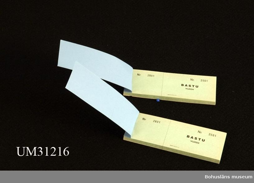 Blått biljetthäfte med tunna gröna biljettblad som rivs av. Med förtryckta texten:  BASTU VUXEN