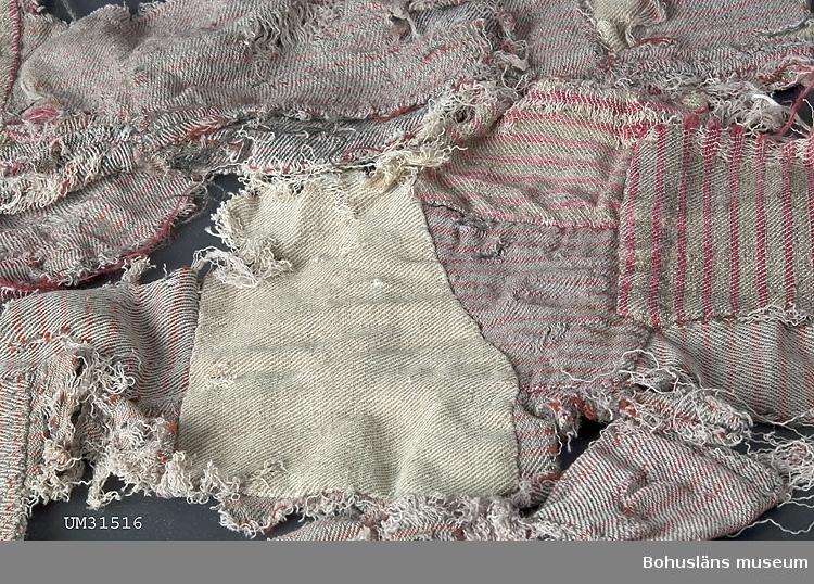 Delar av en ytterligt trasig skjorta i halvylle, randning i rött- och brunt ylle på bomullsvarp. Del av halsringning och knappslå fram återstår. Skjortan lagad och förstärkt för hand många gånger med smålappar av kypertvävd halvylle och bomull. Trasorna är tvättade av givaren.  Jfr. UM027492 Tätning.