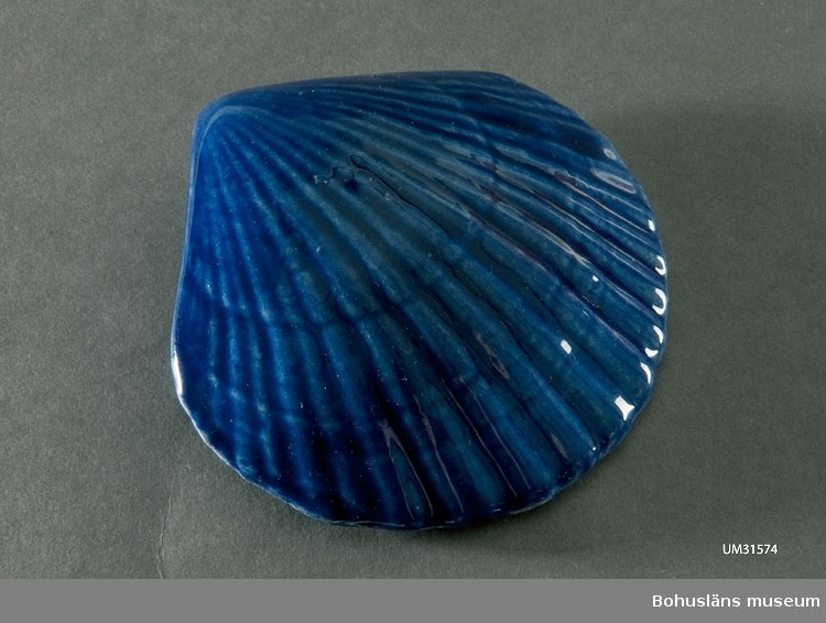 Prydnadssnäckor och av glaserad keramik. En vit, slät snäcka (UM031574:001),  en blå räfflad snäcka (UM031574:002),  en vit fem-armad snäcka  (UM031574:003). Måtten avser den vita snäckan. Okänd tillverkare. På butikens följesedel benämnd: Snäcka Cadiz, stor.  Inköpta i Lysekil  till föremålssamlingarna i samband med utställningen Fri och ledig!? sommaren 2011.