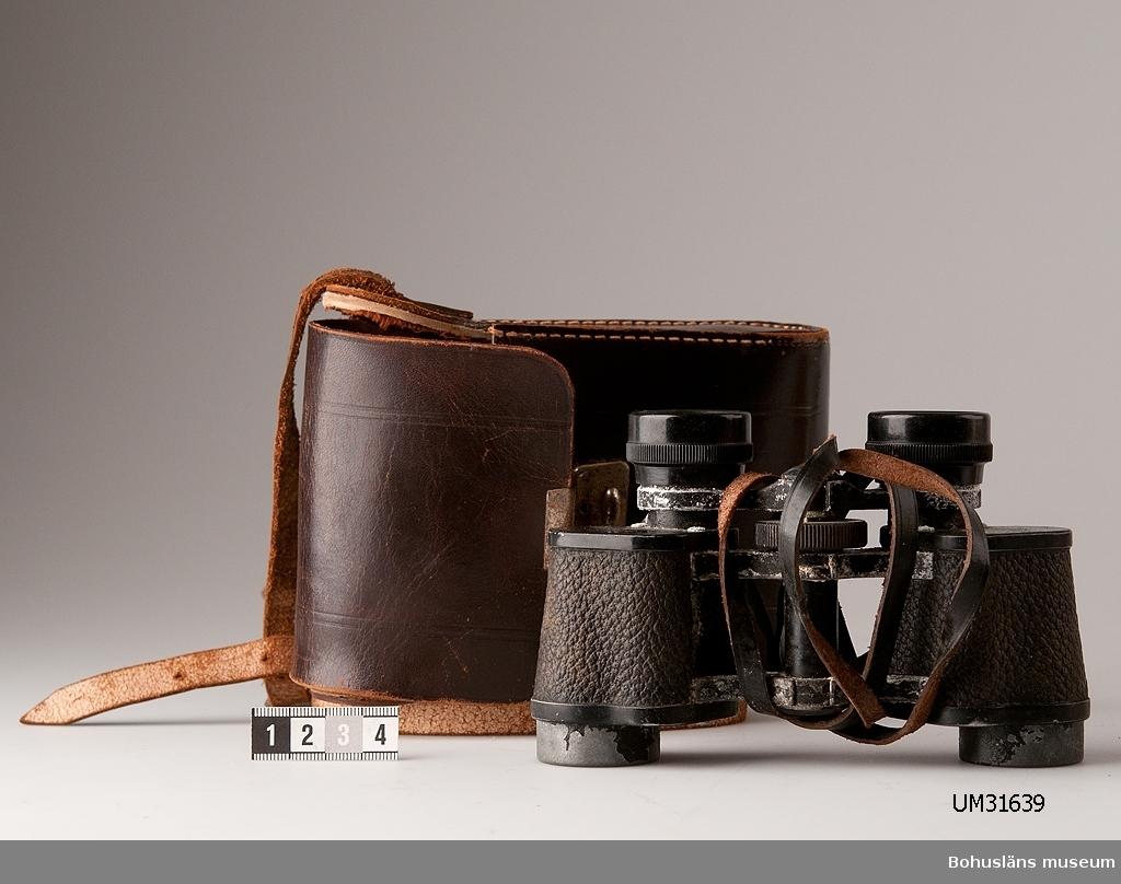 """Kikare i brunt läderfodral med rem och knäpplås. Kikare, fabriksmärkt """"RUKA Rathenow"""" och """"MARS 6 x 24"""", med läderrem. Korrossion."""