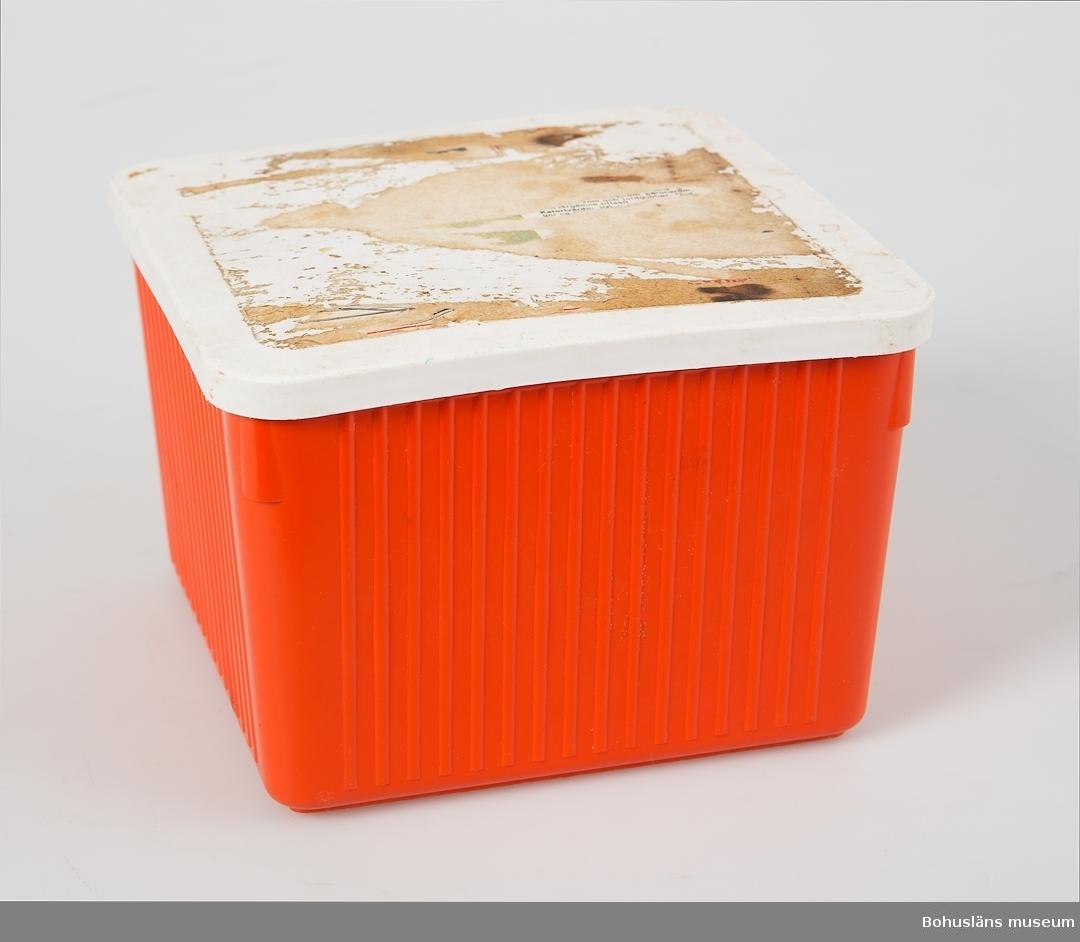 """Kvadratisk låda av hårdplast med vitt lock av mjukplast. Har från början troligen varit en glasslåda. På locket rester av pappersetikett.  I botten märkning """"HAUSTRUP PLASTIC""""."""