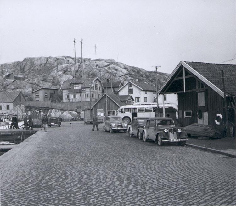 """Notering på kortet: """"Hamngatan ca. 1950. Bilden tagen mot Bäckevikstorget där brandstation låg mitt på torget""""."""