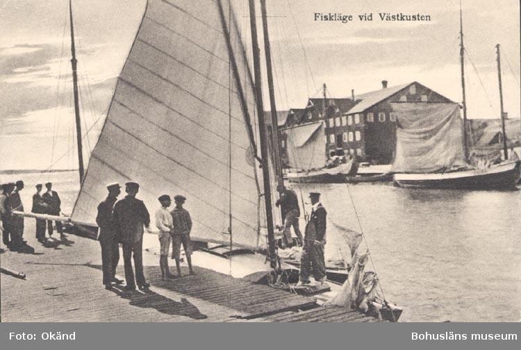 """Tryckt text på kortet: """"Fiskeläge vid Västkusten"""". Noterat på kortet: """"SMÖGEN"""". """"Förlag: Albert Wallins Bokhandel, Lysekil""""."""