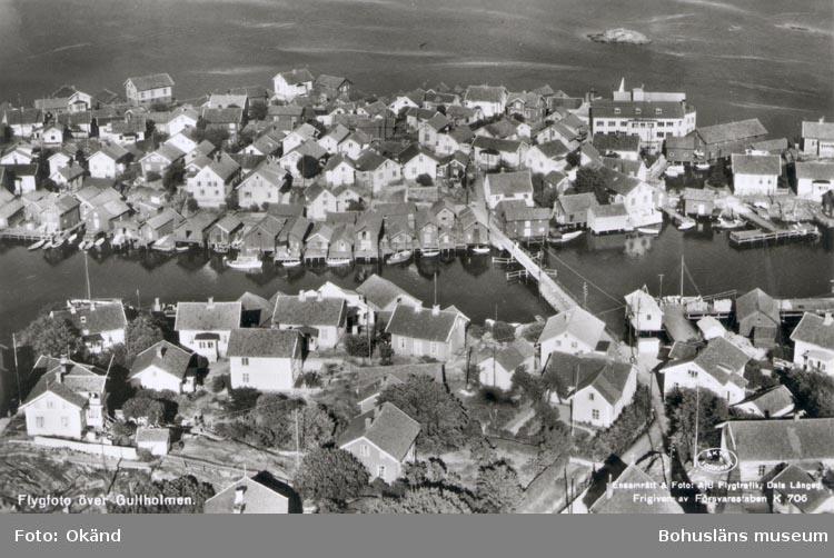 """Tryckt text på kortet: """"Flygfoto över Gullholmen"""". """"Ensamrätt & Foto A/B. Flygtrafik. Dals Långed. Frigiven av Försvarsstaben K 706"""".""""."""