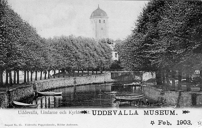 """Tryckt text på vykortets framsida: """"Uddevalla Lindarne och Kyrktornet""""."""