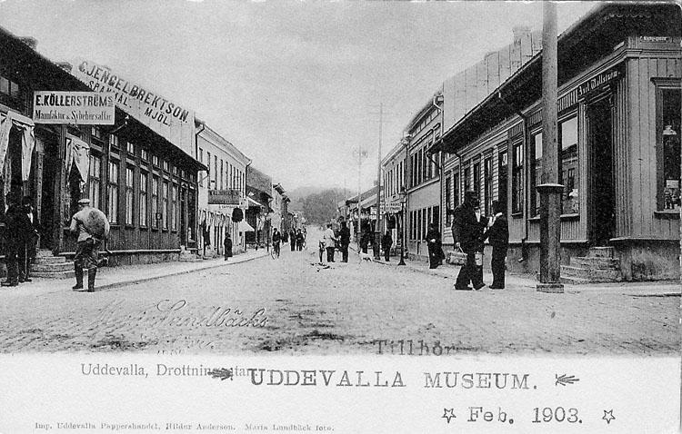 """Tryckt text på vykortets framsida: """"Uddevalla, Drottninggatan""""."""