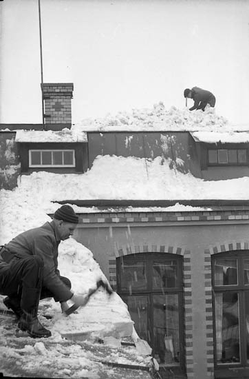"""Enligt fotografens notering: """"Snöskottare på tak 1966""""."""