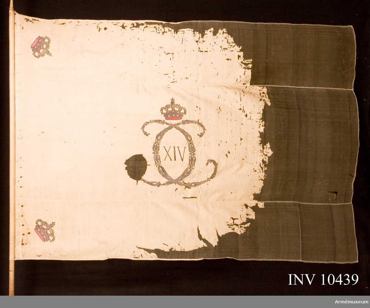 Grupp B.  Fanduk av vit sidenkypert varå broderat i guld lika å båda sidor, ett av små ornament bildat spegelvänt C samt XIV, ändrat från XIII, däröver sluten krona med rött foder, pärlor i silver, stenar i olikfärgat silke. Kronor i hörnen liknande de föregående. Duk i tre våder. Stång av furu, vitmålad. Stången inkom 18790228. Längd med crepelin 270 cm resp. utan 259 cm. D:o bredd 200 resp. 151 cm. Klack av mässing 8 cm. Holk 9,5 cm, saknas. Spets av förgylld mässing med Karl XIV Johans namnchiffer. Spetsen avbruten en gång och tillgjuten till en enkel spets. 14 cm.