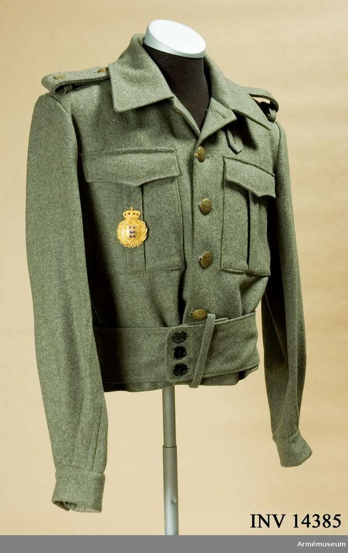 """Grupp C I. Blus, fält-, menig, Danska brigaden, Danmark. Med brigadmärke. Av khakikläde. Enradig m 4 knappar. Längs nederkant ett fastsytt bälte, b: 90 mm, som knäppes m 3 knappar. Axelklaffar av samma kläde, l: 130 mm, b: 30-40 mm, som fästes vid blusen m knappar. Nummer på klaffen """"2"""" =bataljonsnr. Fickor på framsidan, 2 raka m lock, stänges m knappar. Fickorna har vertikala motveck. Foder saknas. På blusens insida finns broderade nr """"48"""" =storleksnr. Knappar av gulmetall m graverat danskt statsvapen, tre lejon, d: 25 mm, 5 st på bröstet, d: 15 mm, 2 st på axelklaffar och 2 på ärmuppslag. På klädesbältet finns 3 svarta benknappar på framsidan. Krage, öppen, nedvikt, liggande, av samma kläde.  Ärmuppslag rakskuret m inskärning och 1 knapp. Tillhörde Danska brigaden under 2:a världskriget. Brigaden fick svenska uniformer under kriget."""