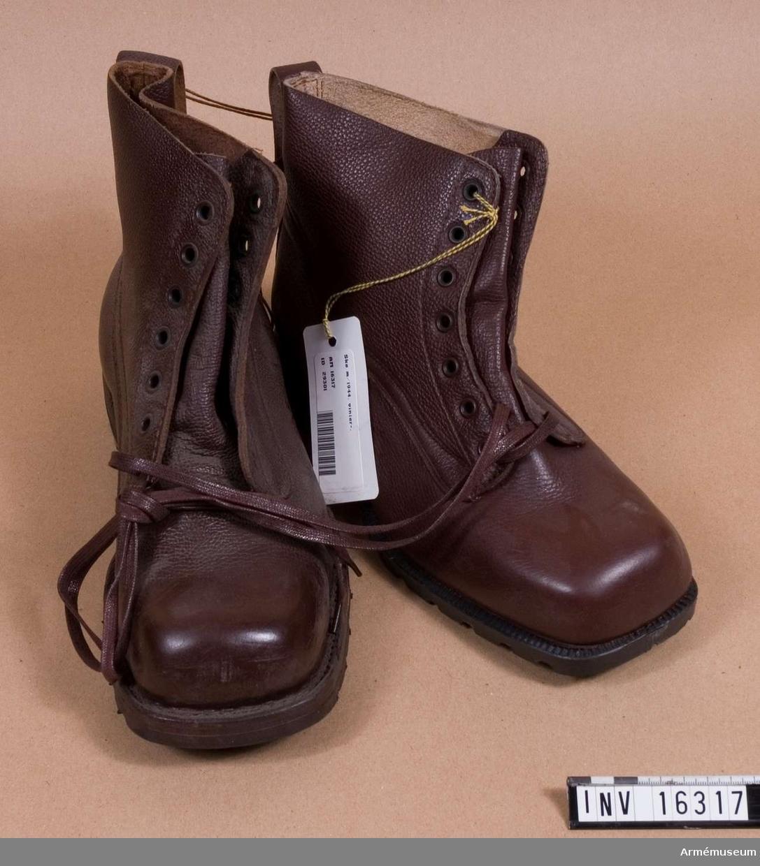 Av tunt brunt läder, med snörning och kraftig gummisula. Urtag i klacken för skidbindning. Storlek 43.
