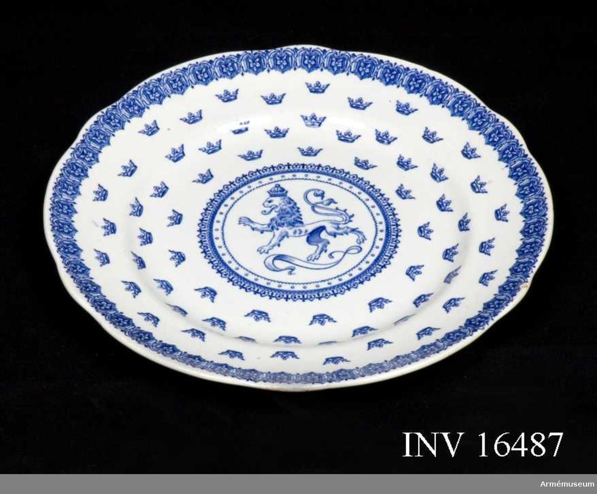 Tallrik av vitt porslin med fasonerade kanter och blå dekor, modell: Svea.  Tillverkad någon gång omkring år 1900. I botten riksvapnets lejon omgivet av cirkeldekor. Fem rader med adelskronor täcker  botten och brämet avslutas med en bård i form av sköldar. På undersidan Rörstrands stämpel (både stämplat och målat) samt tallriksmodellens namn och dekor och beteckningen A 09 1/2.