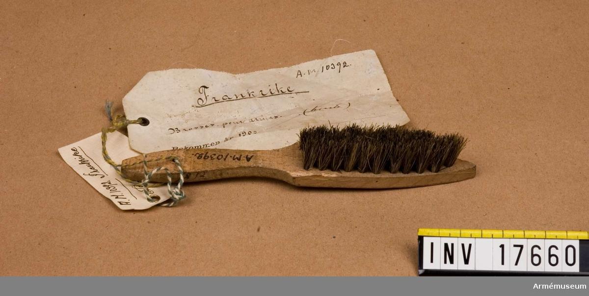 """Grupp C II. Borste för vapen, Frankrike. 1903. Borste för att putsa vapen och utrustning av kort grå svinborst. För manskapspackning.  Borsten har en pappersetikett på vilken står: """"Frankrike. Brosses pour armes"""" - borste för vapen. """"Bekommen år 1903"""".  Med blyerts över 'Bekommen': """"Erhållen (?)""""."""