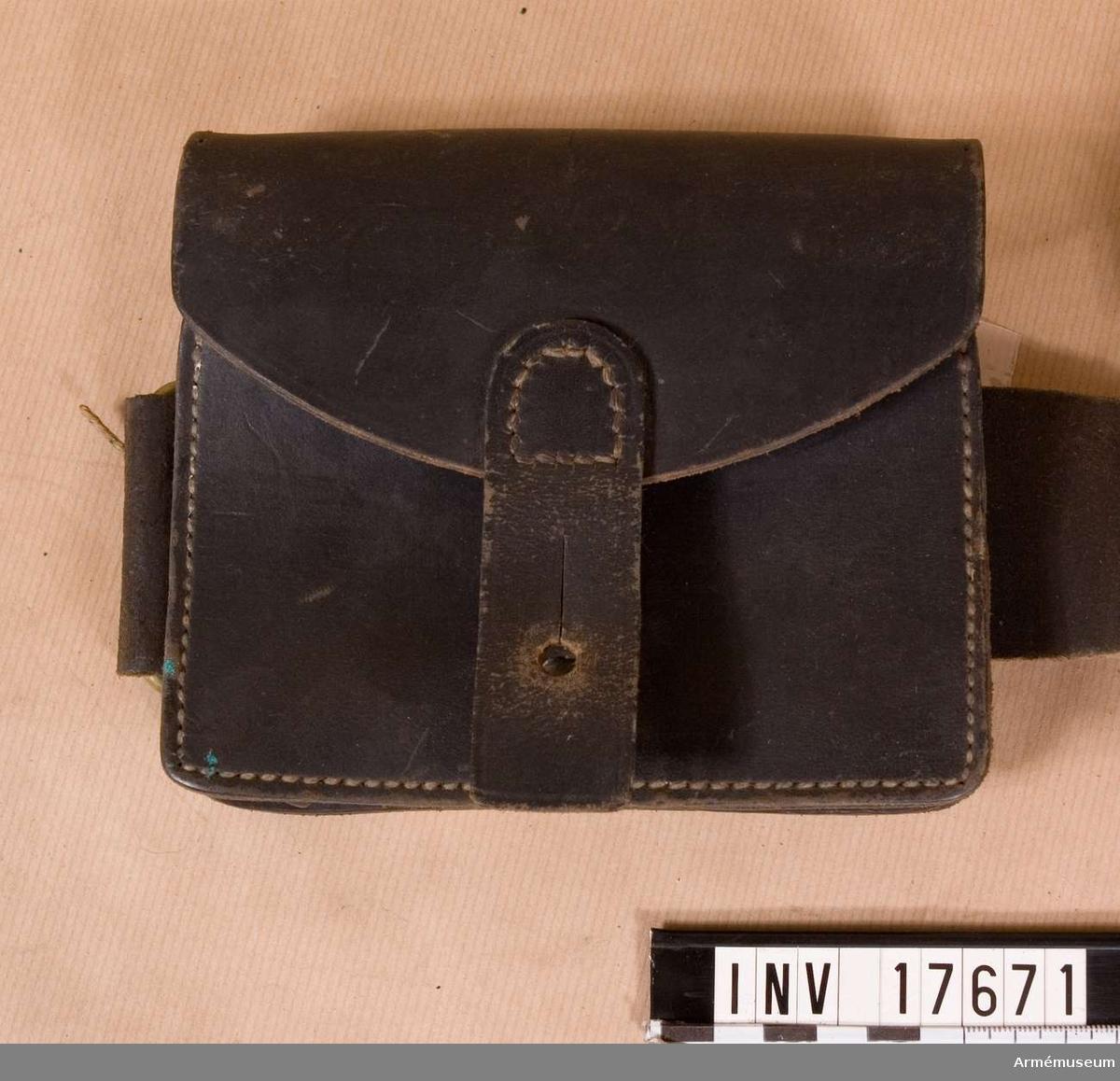"""En av tre patronväskor av svartfärgat läder (till Lebelgevär m/1886). De består av lock: detta har en läderbit med knapphål, som stänges på framsidan. Väskorna på framsidan en knapp och på baksidan en bred hylsa av samma läder, med vilken man fäster  dem vid livremmen sammt en ring, som kopplas till  tornisterremmen. På baksidan av patronväskornas lock finns  stämplar:1) halvrunda: """"Commission de réception"""" 12.8.1899"""" 2) intryckt stämpel: """"1899"""" 3) rund med påskriften: """"A. Cendrov. F.F. Gurnier & Co Paris"""", 4) liten rund med bokstäverna: """"G.P.K."""".Patronväskorna har pappersetiketter med påskrifter: """"Frankrike. Cartouchiens"""" (patronväska) """"Bekommen år 1900"""" """"Frankrike. Ceintouron avec plaque verron et porte-epée bajonette"""". Litteratur: Se 17669. Enligt kapten W Granberg (med blyerts: 1949)."""