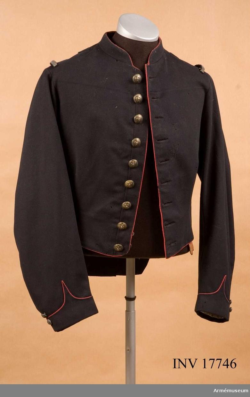 """Grupp C I. Frack för officer vid kavalleriskolan i Saumur, Frankrike. Frack (vapenrock) av mörkblått kläde, enradig med nio knappar, 45 cm lång, åtsittande. Framtill passpoal från kragen ända ned och längs nedre kanten - i röd färg.  Epålettslejf av silvergalon, 1 cm bred. Foder av gult bomullstyg. Vid rockens nedre kant finns en fastsydd remsa av brunt läder, 5 cm bred. Rocken har ett bälte av läder med två hyskor och hakar. På vänstra sidan finns en liten ficka av kläde. På fodret vid kragen finns påskriften: """"Staffsen"""".   Knapparna är av vit metall med den kejserliga franska örnen. Runt knappen en ingraverad påskrift: """"Ecole imp:le de  cavalerie"""". Med 2 cm:s diameter: nio knappar på bröstet och fyra på skörten. Med 1,5 cm:s diameter, två på varje ärmuppslag.  Kragen är upprättstående, 3 cm hög av samma kläde med halvrunda beläggningar. På kragens övre kant finns en röd passpoal. Kragen är försedd med hyska och hake samt fodrad med svart sammet.  Skört av samma kläde; de består av två delar, båda kantade med röd passpoal. På vart och ett finns med silvertråd broderat två flammande granater. Där finns också en liten slejf kantad med röd passpoal; den har två stora metallknappar. Ärmuppslagen är av samma kläde, 4 cm breda med vinkel, kantade med röd passpoal och försedda med två knappar på varje."""