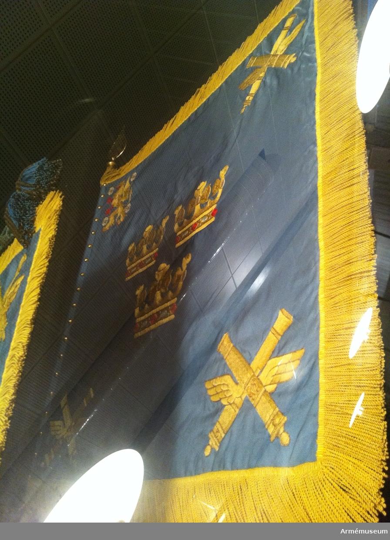 Standaret är handbroderat och dubbelsidigt i blått siden. Motivet är i mitten tre gula, öppna kronor ordnade två och en. I de båda ytterhörnen och i det nedre hörnet två gula, korslagda bevingade kanoner. I det övre inre hörnet landskapet Östergötlands vapenbild med fyra stjärnrosor. Standaret har gul frans. Stången är vitmålad och inte delbar.