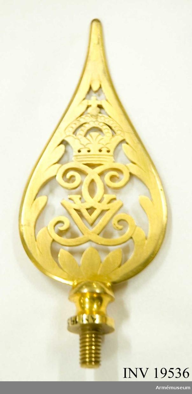 Spetsen är tillverkad av förgylld mässing. Den har Gustav V:s spegelmonogram under en kunglig krona inramat av ett bladverk avslutas i en spets. Spetsen försedd med en skruv. Spetsen tillhör fana AM 19535.  Samhörande nr 19535-38, fana, spets, kravatt, fodral.