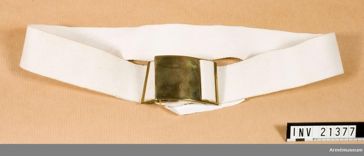 """Samhörande nr är 21374-89 uniform. Samh. köp: 21374-408. Grupp C I.  Neg.nr E 73/23-25. Ur uniform för kadett i West Point, USA. Består av frack, långbyxor, kappa, skärmmössa, tschakå med ståndare, tygfodral, vantar, livrem med spänne, fältmössa.  Buren av Richard A Gillespie.Av vitt, tjock tyg. Lås-spännen av blank, gul metall. Spännet är kullrigt. På remmen påskrift """"Gillespie - R""""."""